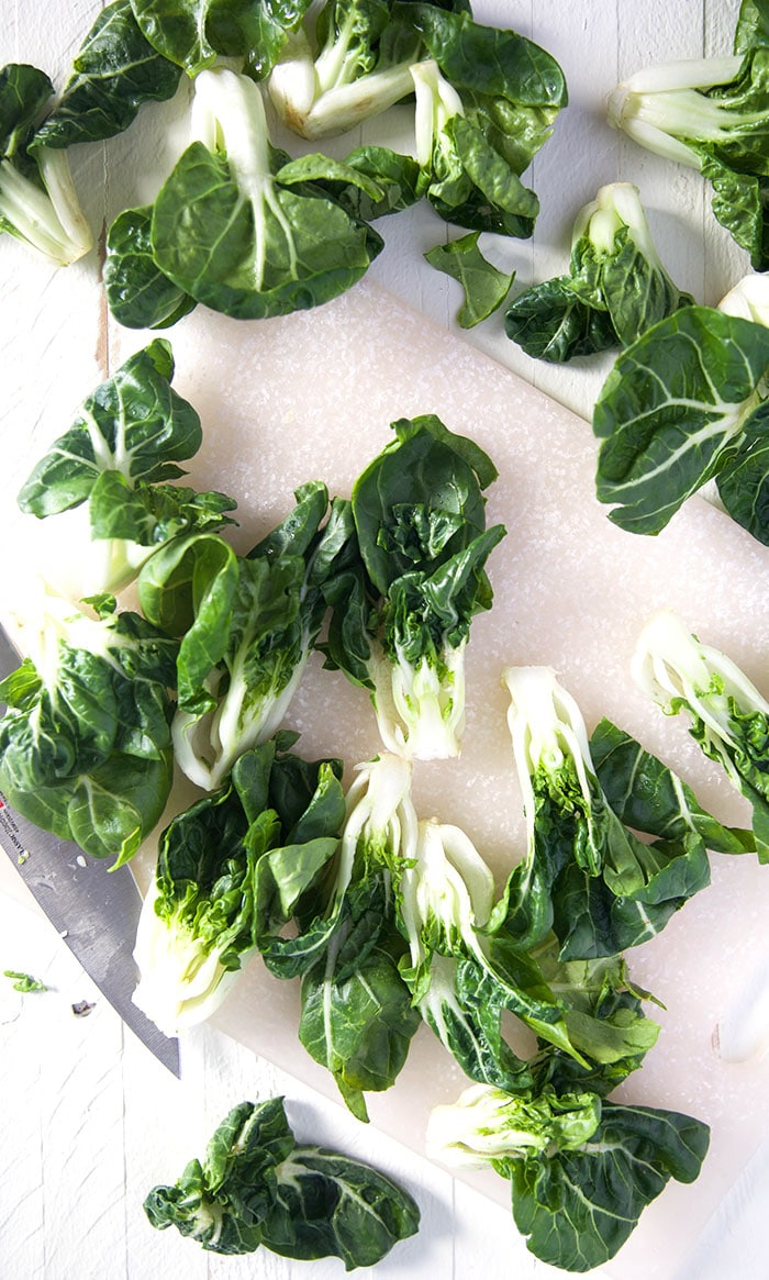 Bok Choy is spread out on a white surface.