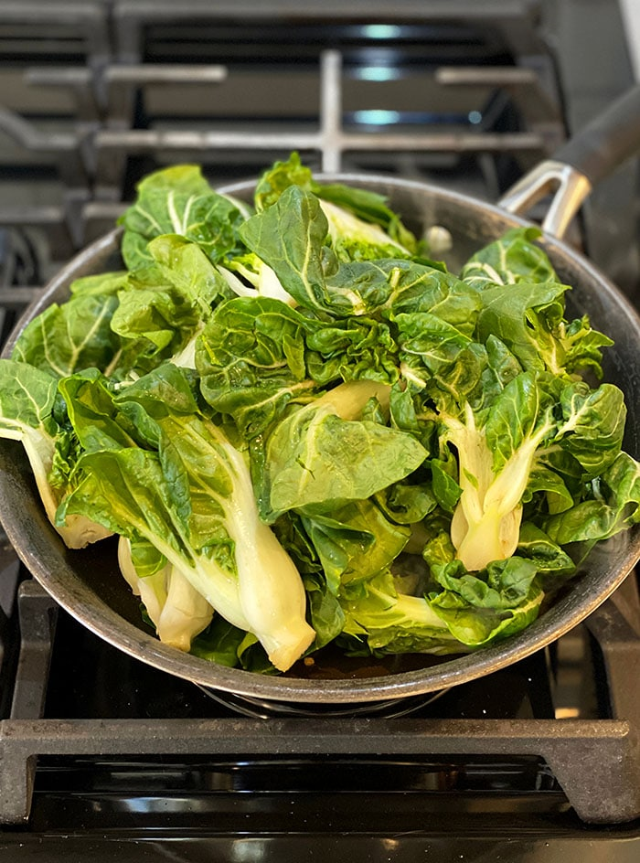 Bok Choy is in a skillet, ready to be cooked.
