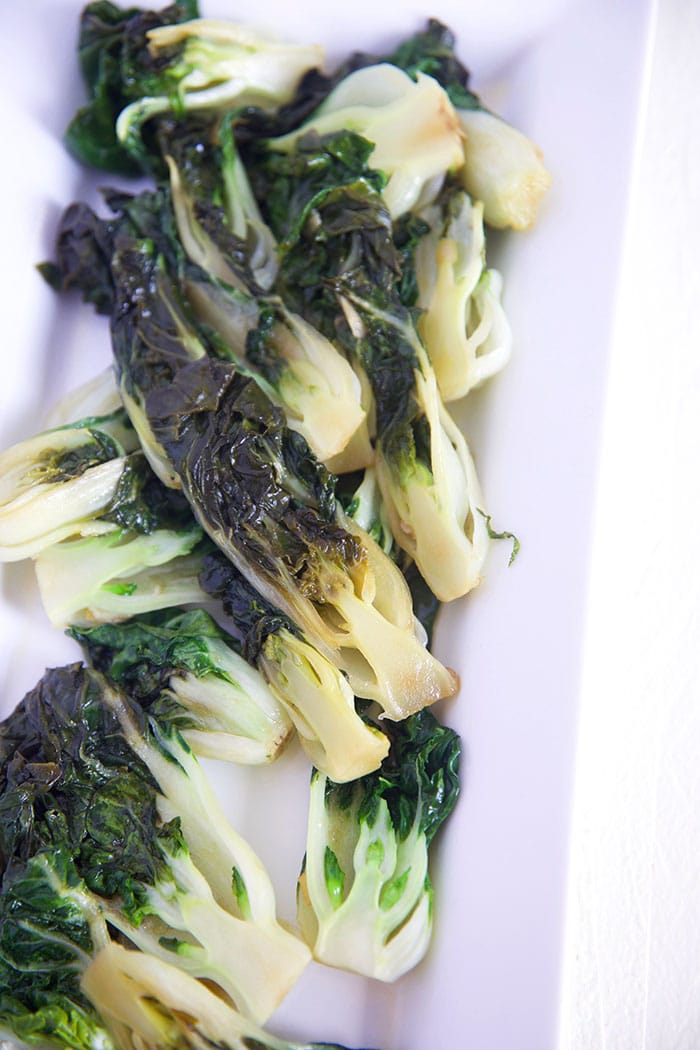 Multiple pieces of sautéed Bok Choy are placed on a serving dish.