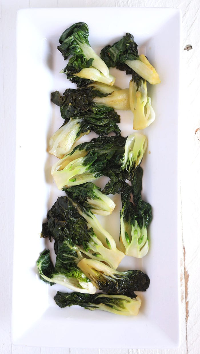 Cooked Bok Choy is presents on a white serving plate.