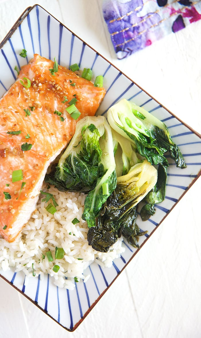 A piece of cooked salmon is presented on a plate, next to bok choy and white rice.