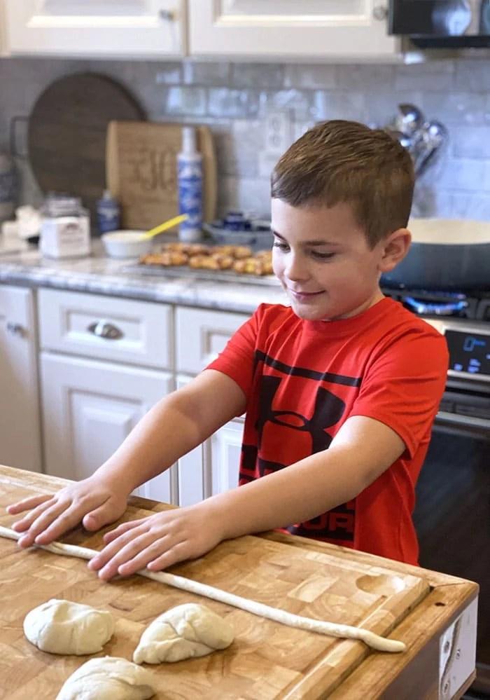 boy rolling out soft pretzels.