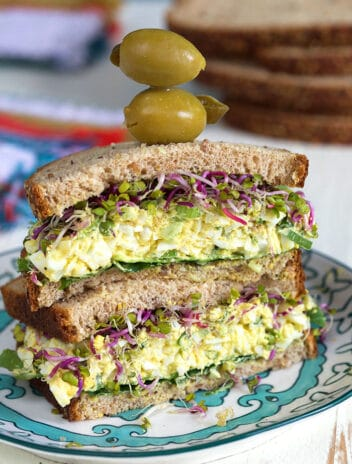 Egg Salad sandwich with olives on top.