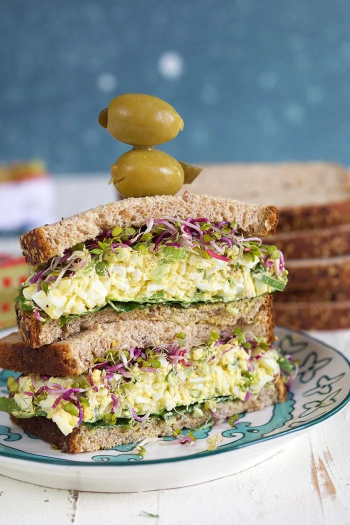 The BEST Egg Salad sandwich with olives on top with a blue background.