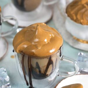 Whipped Coffee Mudslide on a blue background with a gold spoon on a white plate.