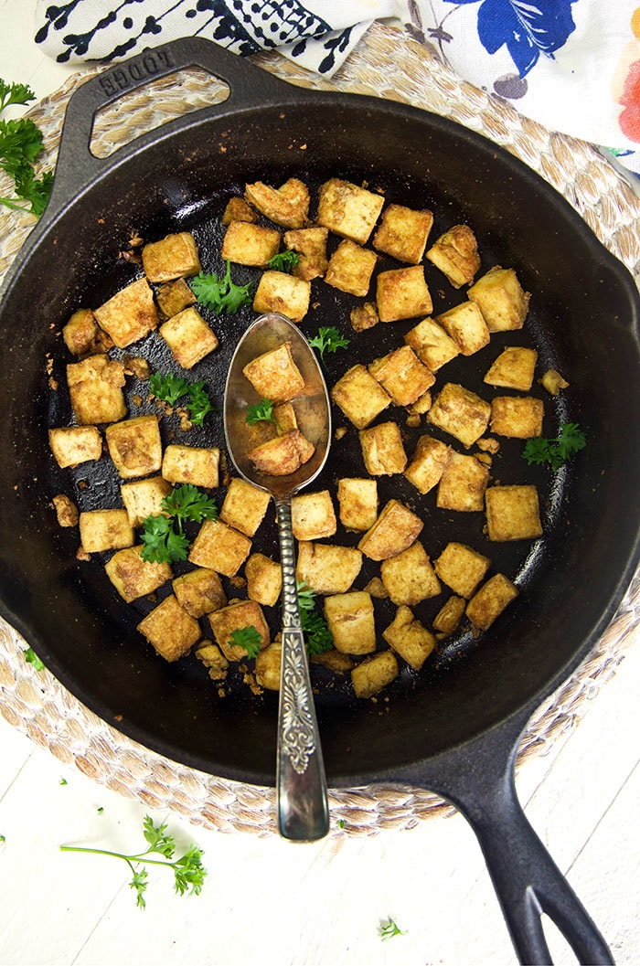 Crispy baked tofu is in a black skillet with a spoon.