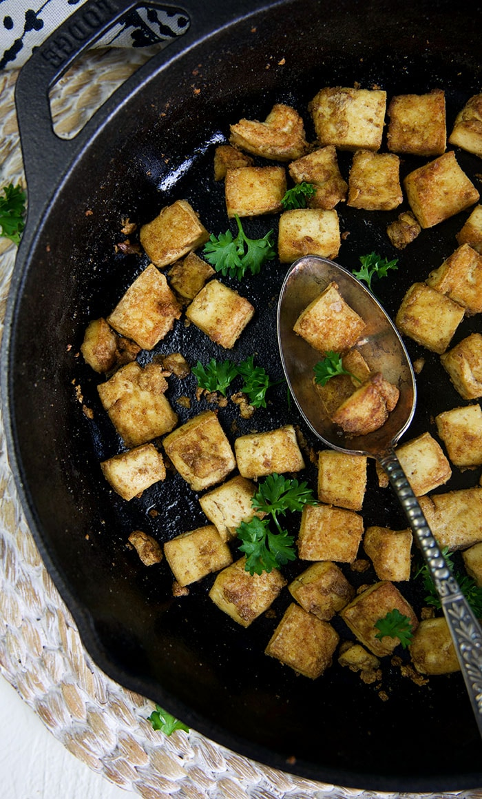 A spoon is placed in a large black skillet filled with tofu.