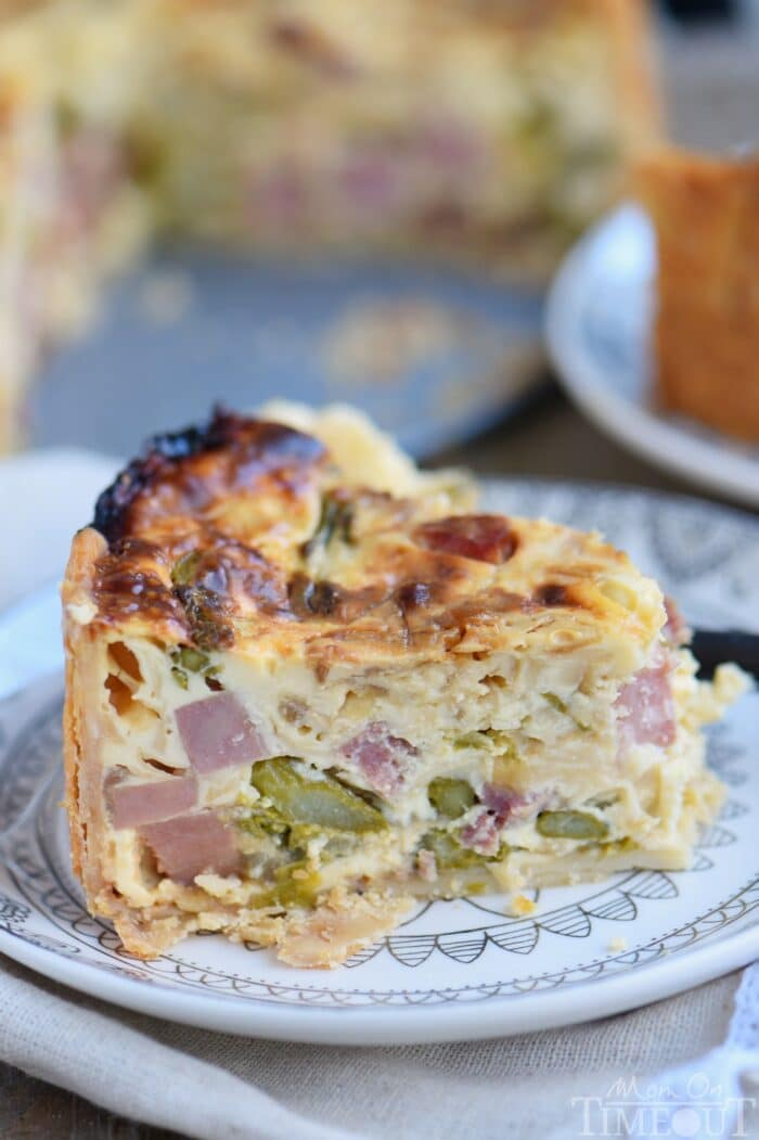 Deep Dish Ham and Asparagus Quiche on a white plate.