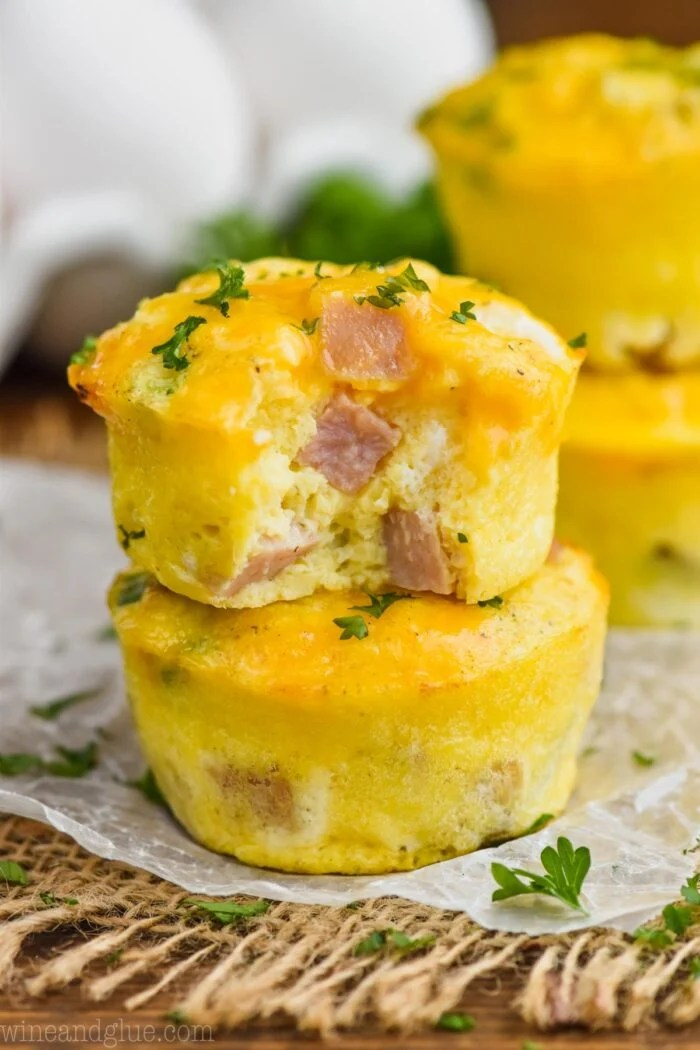 Ham and cheese egg muffins stacked on a piece of parchment.