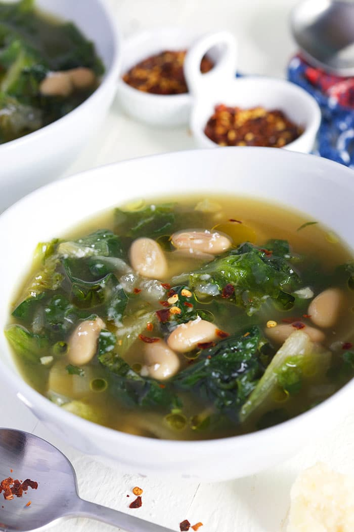 Escarole soup with beans in a white bowl with crushed red peppers in a white dish.