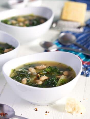 Escarole Soup in a white bowl on a white background.