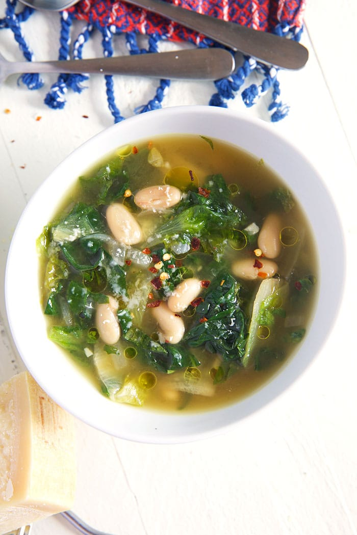 overhead shot of escarole soup with white beans in a white bowl with a blue tasseled towel near the top of the bowl.