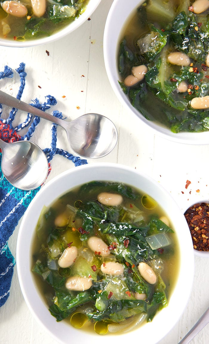 Overhead shot of two white bowls with escarole soup on a white background.