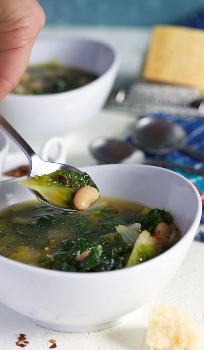 Escarole soup on a silver spoon over a bowl of soup in a white bowl.