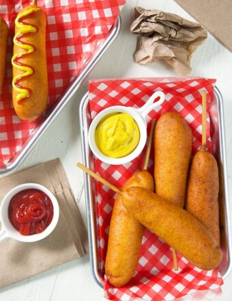 overhead shot of corn dogs on red and white paper with a dish of mustard.