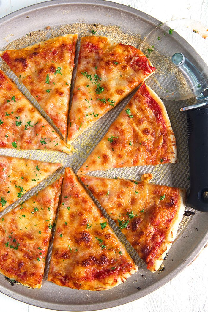 overhead shot of whole thin crust pizza on a pizza pan.