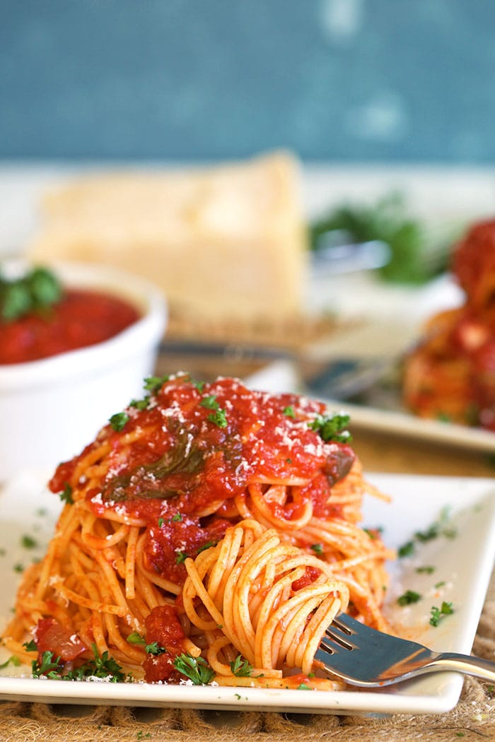 Spaghetti on a white square plate with spaghetti sauce on top and a fork with twirled pasta.