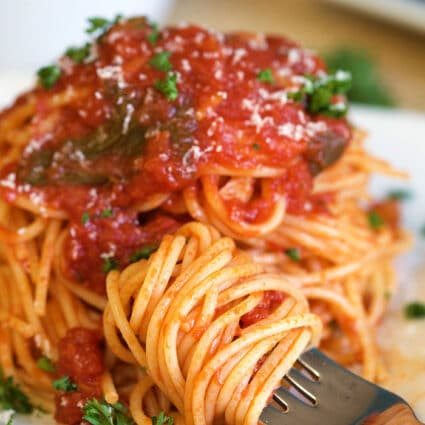 Close up of fork with spaghetti twirled around it on a white plate with spaghetti with spaghetti sauce.