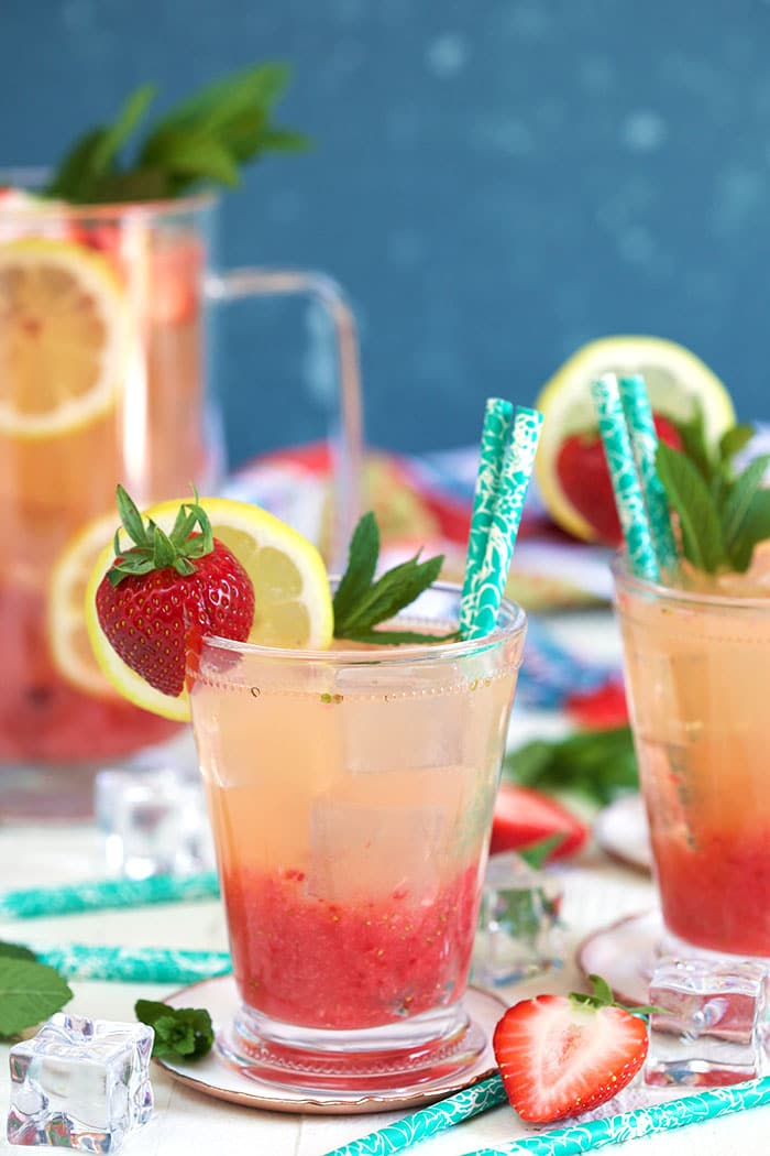 Glass of strawberry lemonade with a strawberry and lemon garnish with a turquoise colored paper straw.