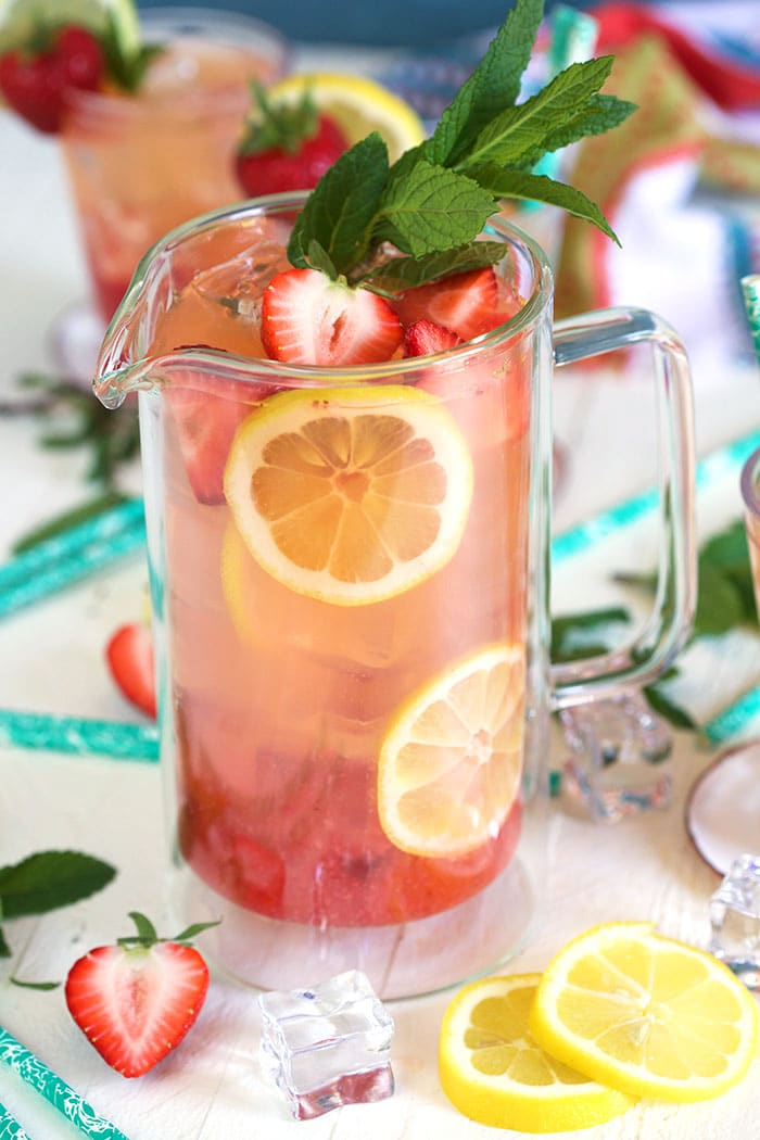 Strawberry lemonade in a glass pitcher with lemons and strawberries arranged in the pitcher as a garnish.
