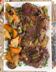 overhead shot of pot roast on a white platter with potatoes, carrots and mushrooms.