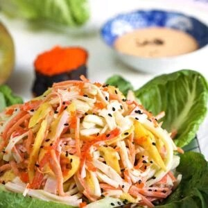 Kani Salad on a bed of lettuce with spicy sauce in the background.