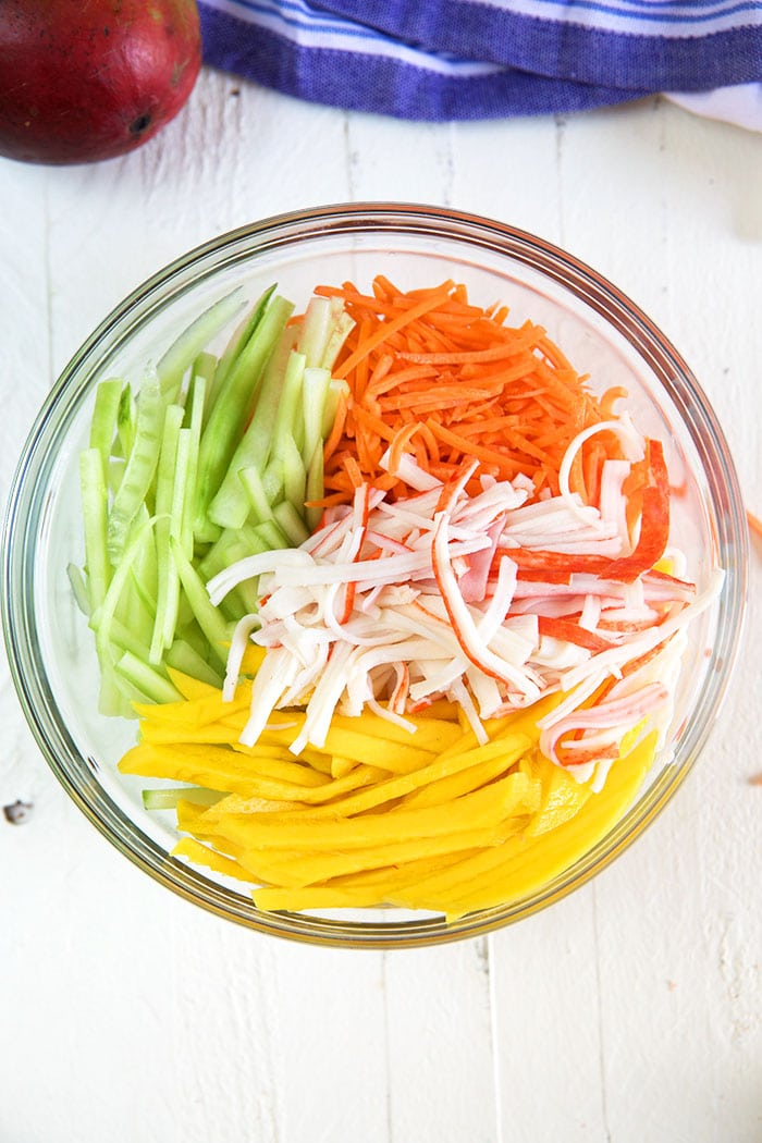 Overhead shot of ingredients for kani salad in a bowl.