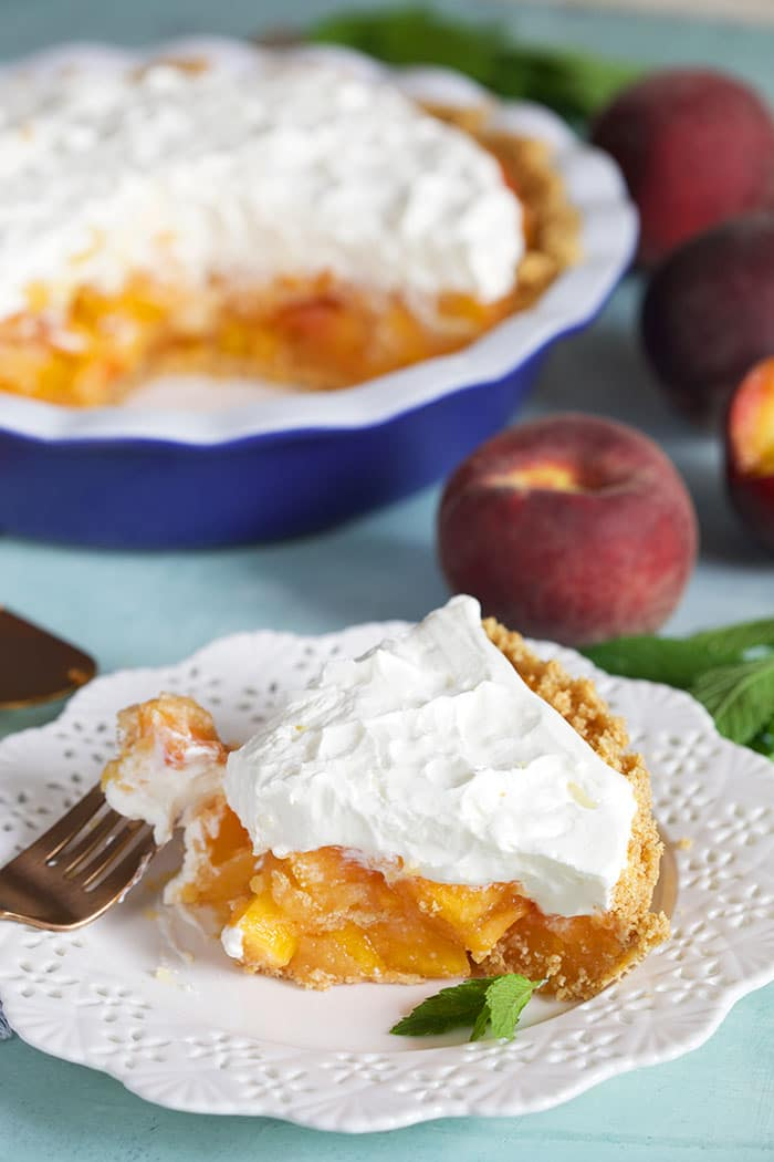 Slice of no bake peach pie on a white plate.
