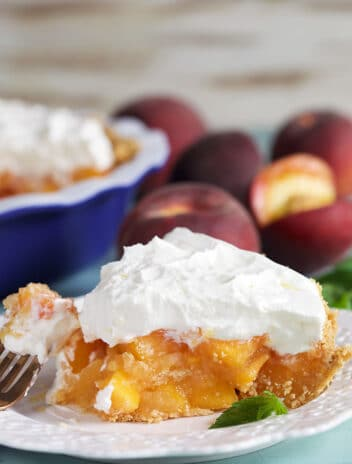 Slice of peach pie with whipped topping on a white plate.