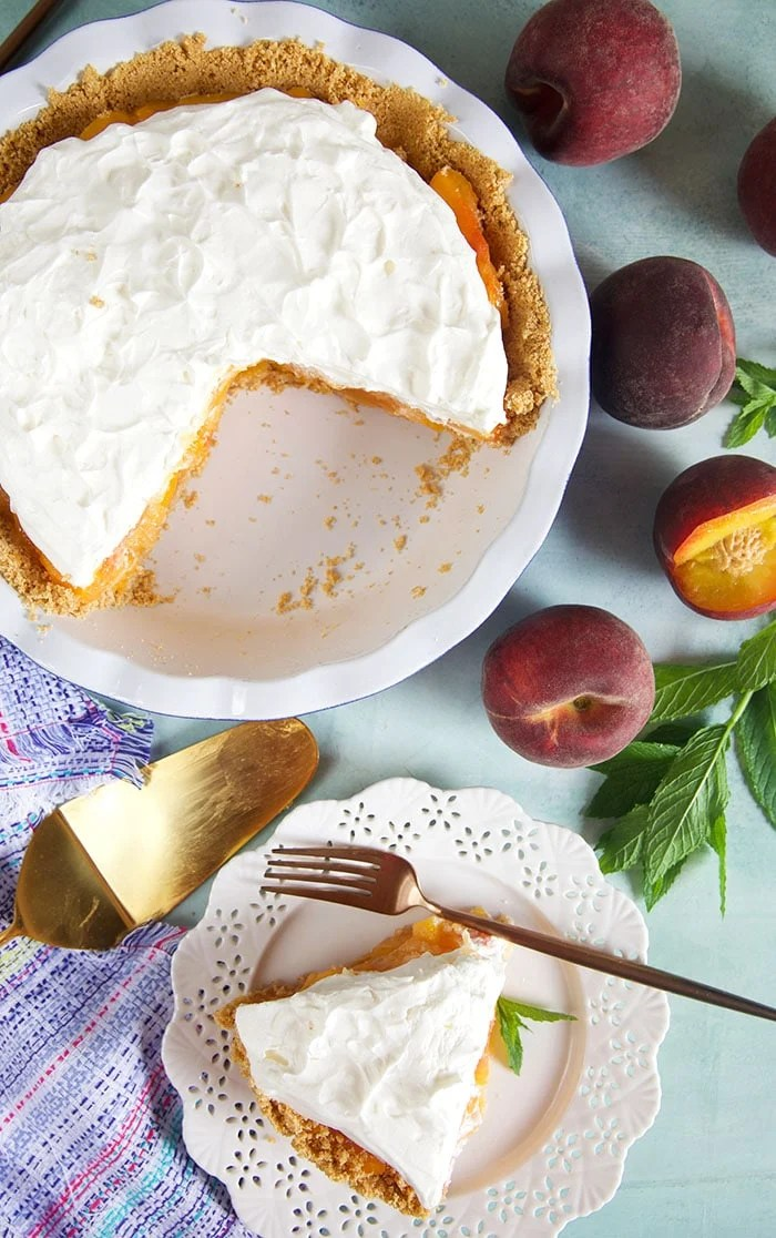 Overhead view of peach pie with whipped topping and a slice on a white plate.