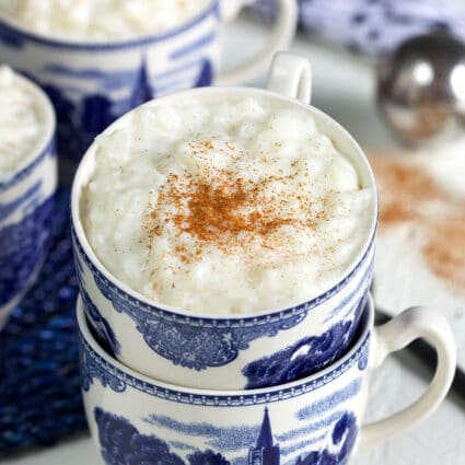 Creamy rice pudding in a blue and white coffee cup with cinnamon on top.