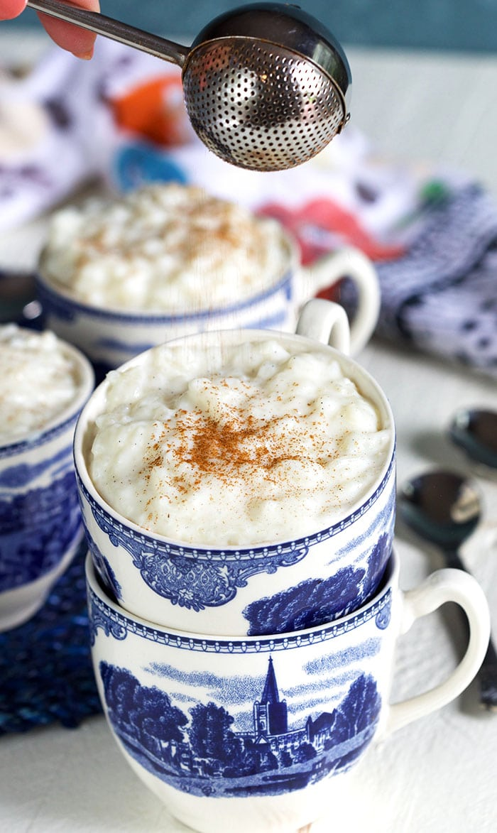 Cinnamon being sprinkled on top of rice pudding in a blue and white mug.