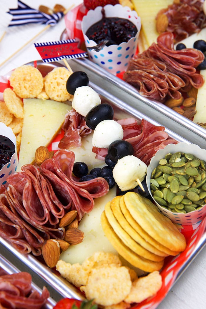 Close up of crackers and charcuterie items on a stainless steel tray.
