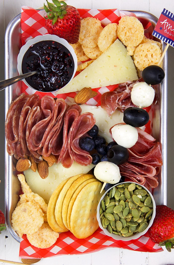 Overhead shot of charcuterie items on a stainless steel board with a red and white paper under the cheese.