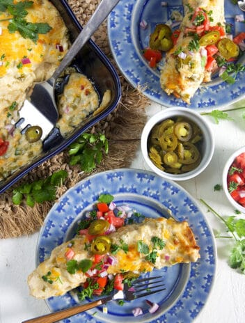 Overhead shot of chicken enchiladas on a blue plate with a wooden fork.