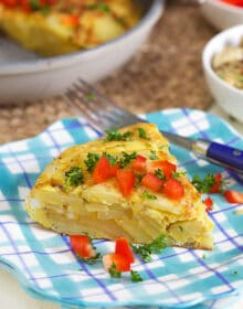 Spanish Tortilla slice on a plaid plate with bell pepper on top.