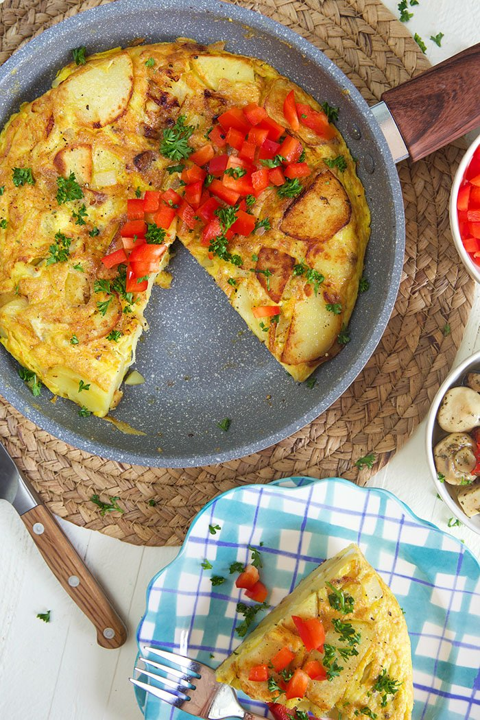Overhead shot of Spanish omelette in a silver skillet with a wooden handle. and a slice of omelette on a plaid plate.