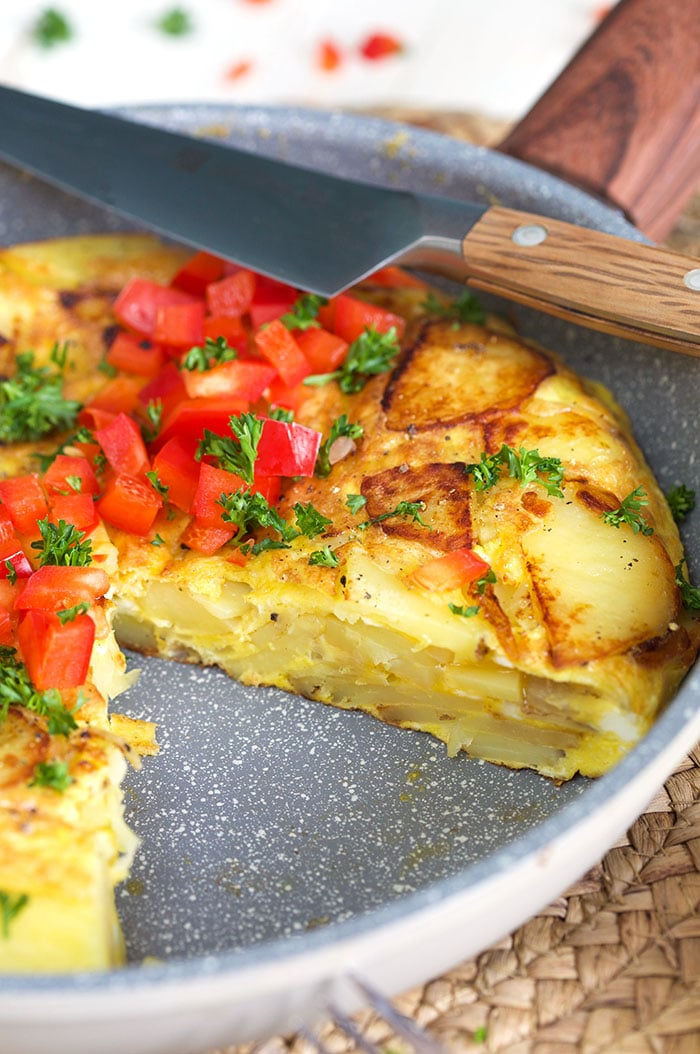Spanish omelette in a skillet with a slice take out and a knife on top of the skillet.
