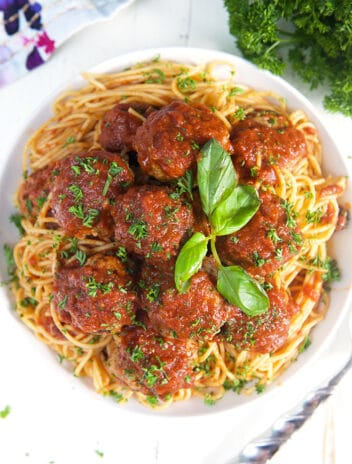 Overhead shot of spaghetti and baked meatballs in a white bowl on a white background.