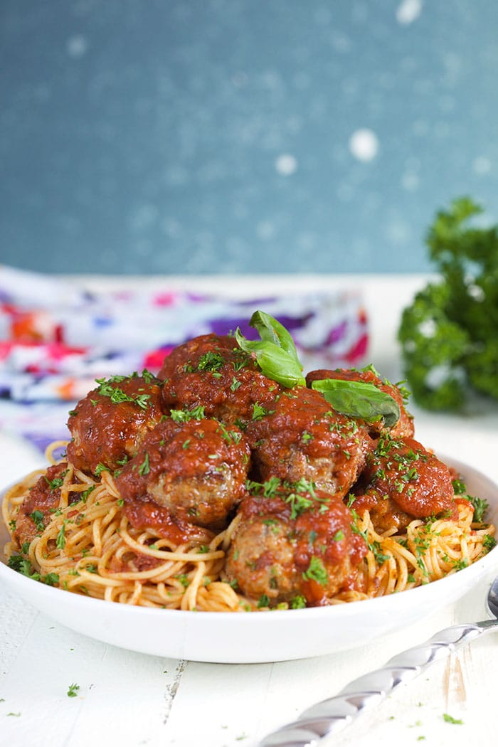 Baked meatballs on top of spaghetti in a white bowl with a blue and white background.