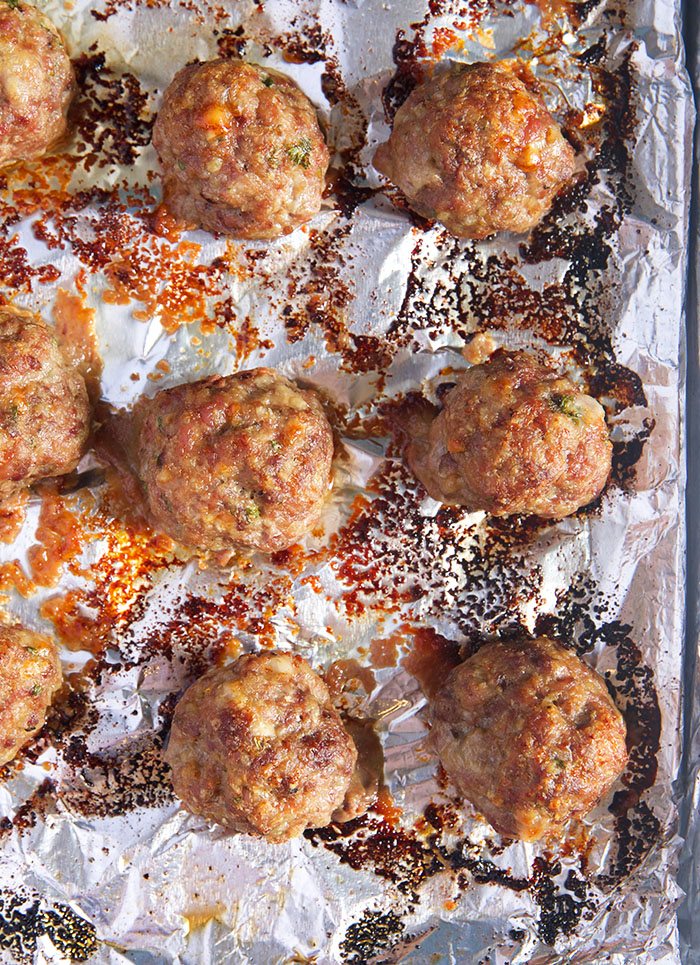 Baked meatballs on a baking sheet with foil.