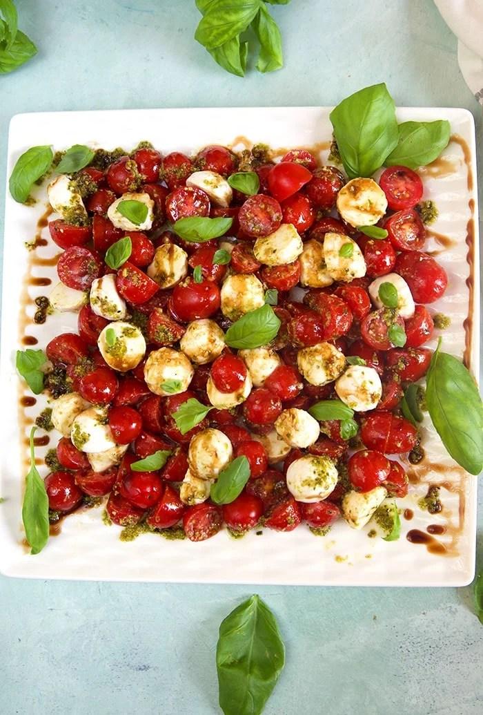 Overhead shot of tomato mozzarella salad on a white platter.
