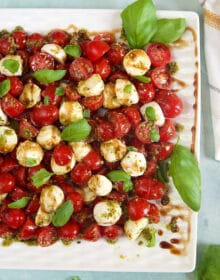 Overhead shot of caprese Salad with cherry tomatoes on a white platter with basil leaves.
