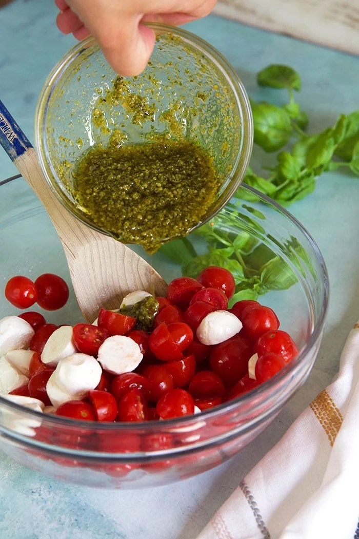 Basil dressing being poured over tomato mozzarella salad.