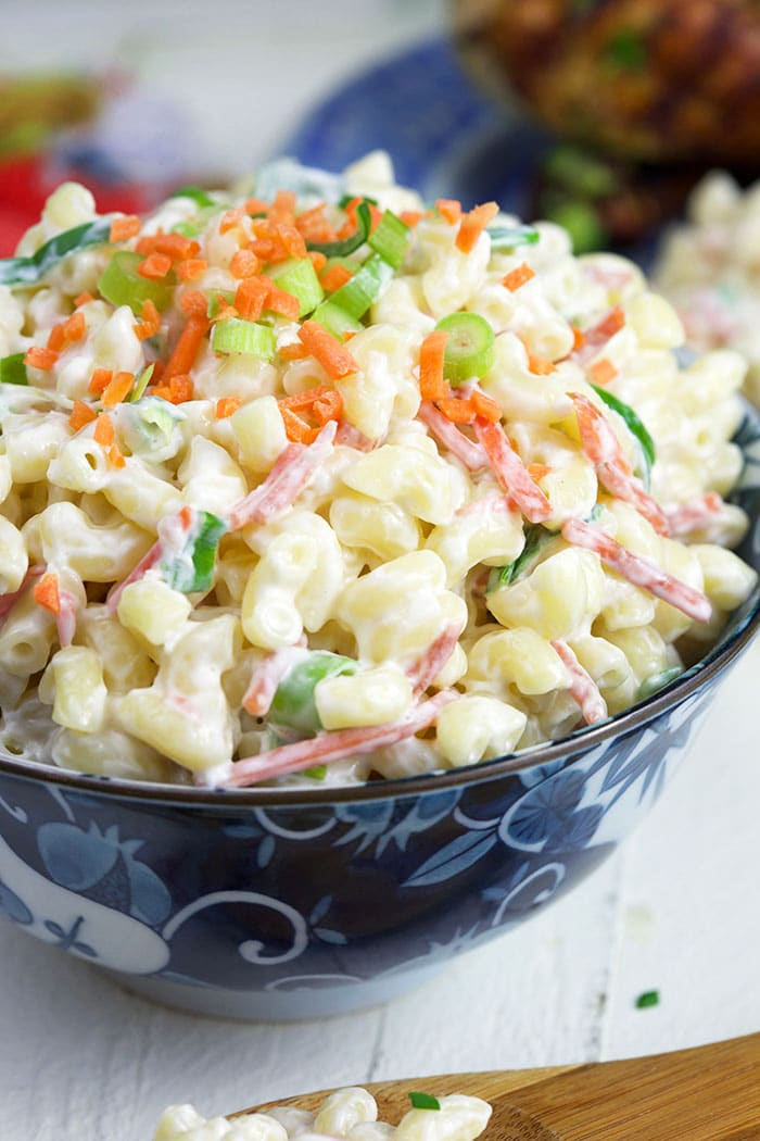 Close up of macaroni salad in a blue and white bowl.