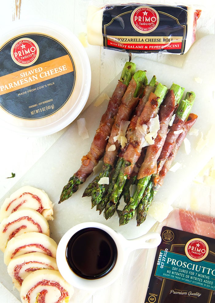 Overhead shot of prosciutto wrapped asparagus with primo taglio products on a white board.