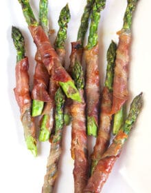 Overhead shot of prosciutto wrapped asparagus on a white platter.