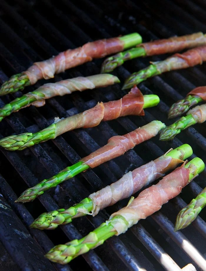 Prosciutto wrapped asparagus on a grill.