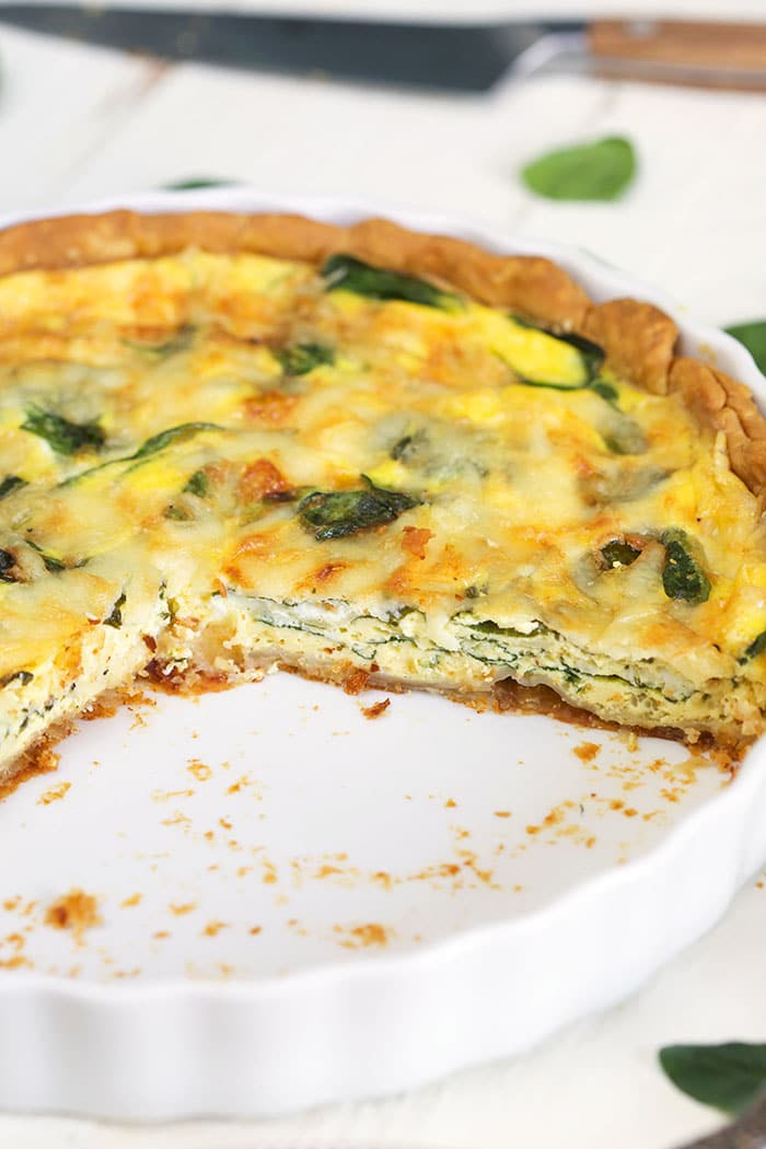 Quiche Florentine in a white pie plate with a slice cut out of it.