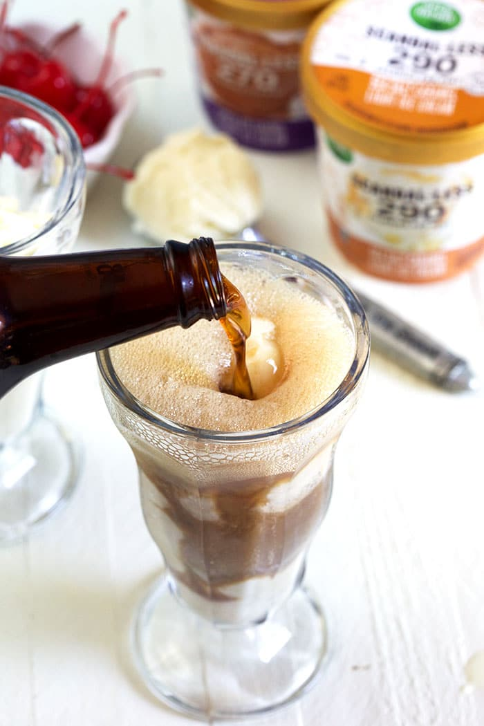 root beer being poured into a soda fountain glass.